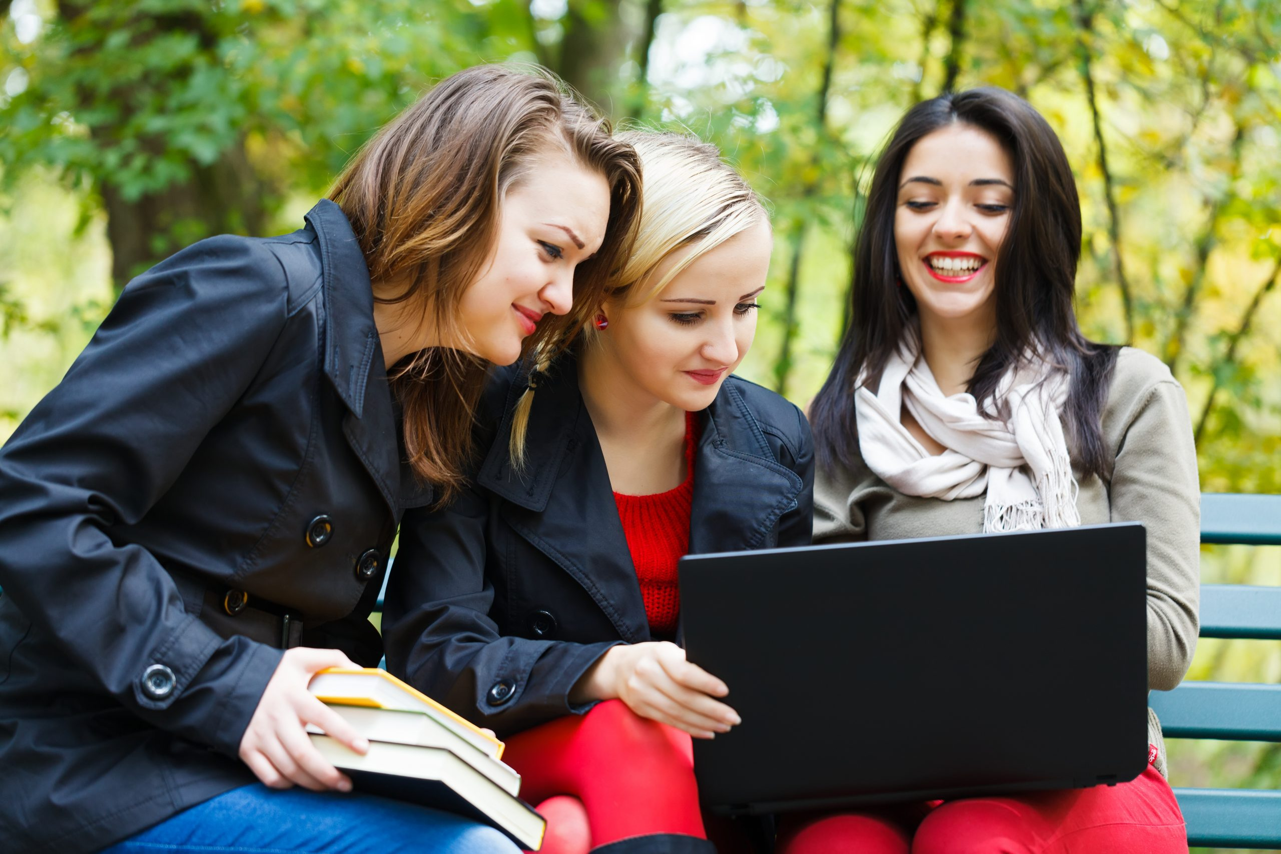 Beautiful girl students with laptops outdoors in the university campus.