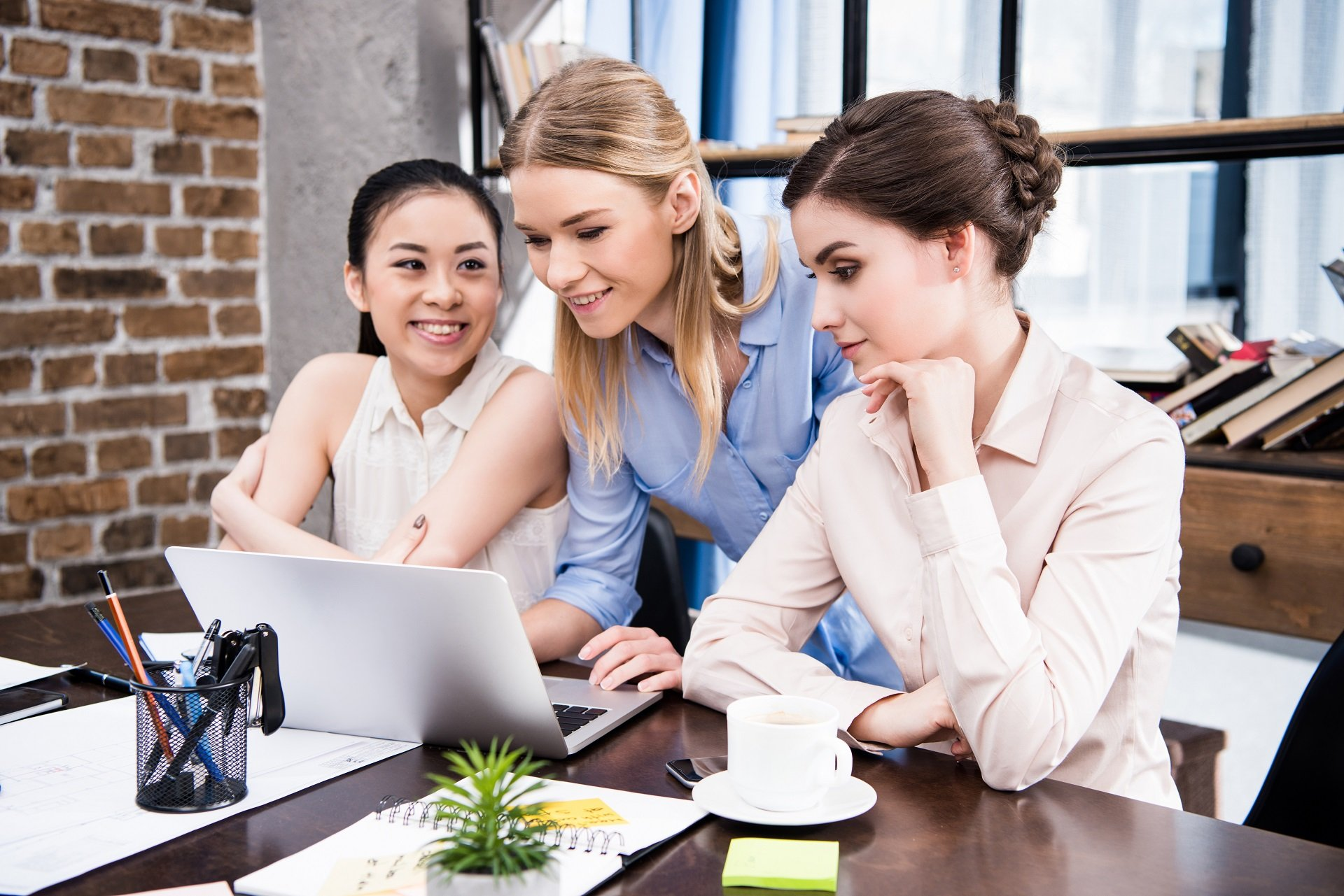 Smiling young businesswomen using laptop together at workplace